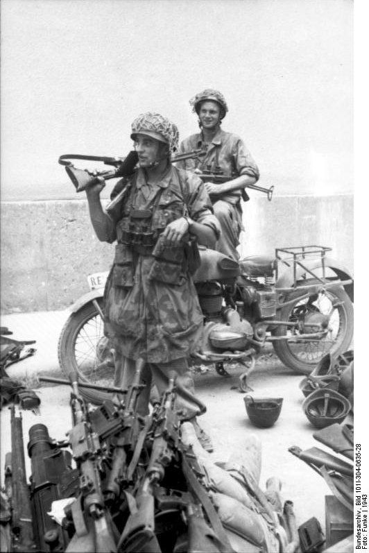German paratroopers with FG 42 rifle and MP 40 submachine gun in Italy guarding a cache of captured weapons, 1943. Among the pile there is a Lewis gun (light MG - the dark cylinder on the left foreground). Note the camouflage oversmock worn by the para in the foreground. Both carry the standard issue Zeiss field glasses.