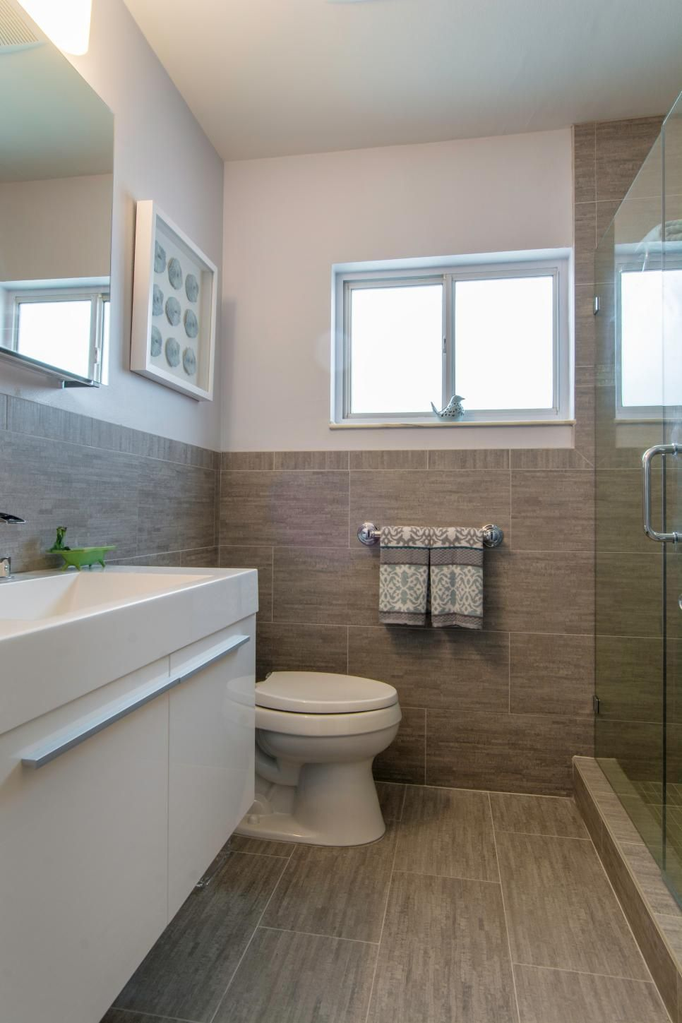 modern bathroom with gray tile and floating white vanity