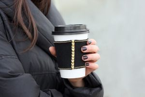 'Don't even mess with me until I've finished this cup of caffeine. Thank you.'     With gold pyramid studs and chain this coffee sleeve speaks for you on your morning commute.  The studs make the most classic of color combinations slightly tough. Just like you.