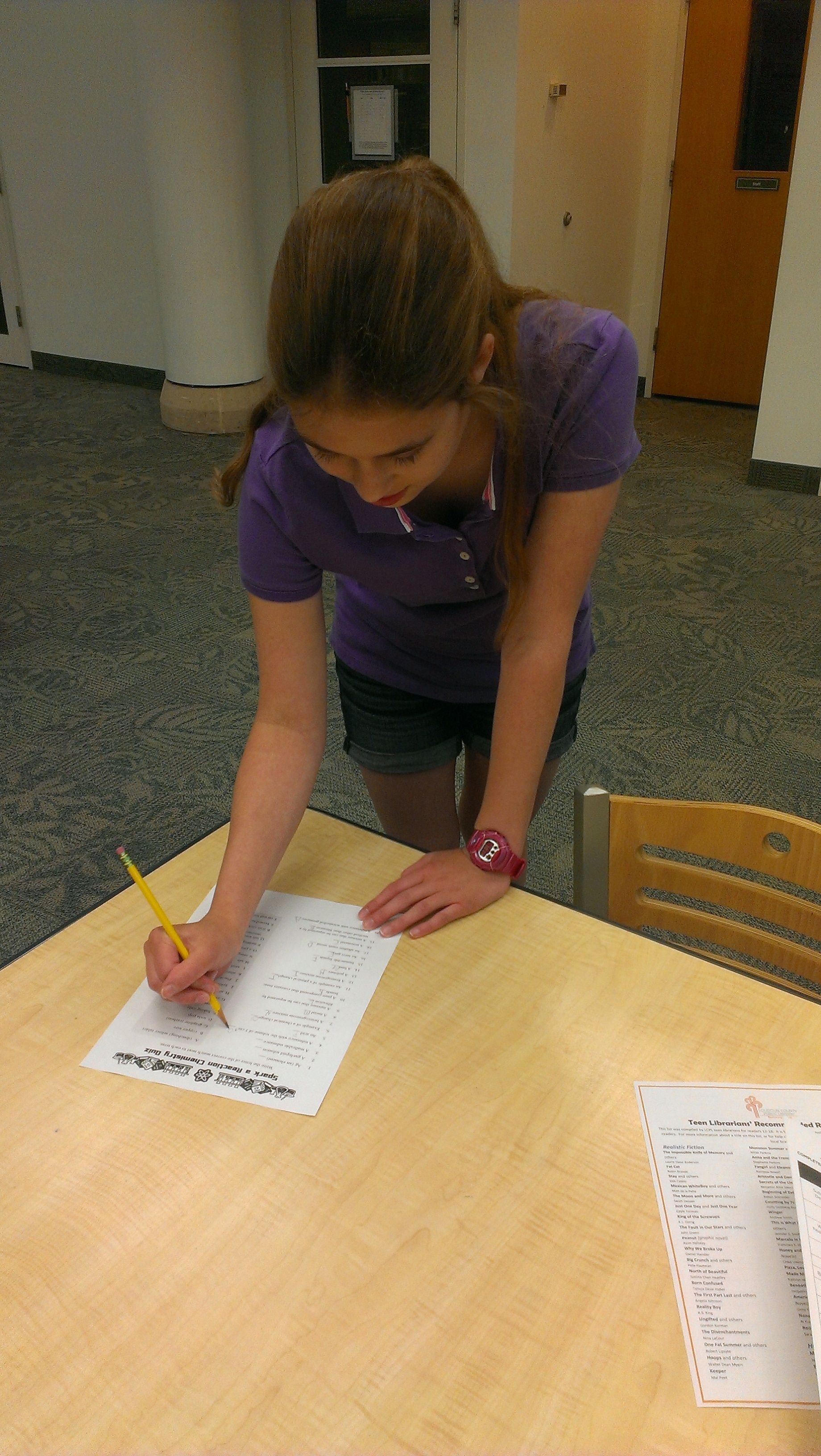 """Teenager participating in a """"Spark a reaction chemistry quiz"""" during summer reading at Cascades Library. For more event and fun visit Cascades online or in person."""