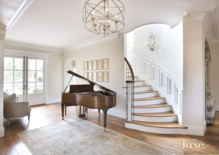 Serving as a focal point in the entrance hall is a curved staircase—featuring handrails from Artistic Stairs, spindles from Creative Metals and decorative accents by Phoenix Molding. A chandelier conceived by interior designer April Lozevski and fabricated by Hinkley's Lighting Factory shines light over the owners' baby grand piano and an Oushak carpet from Azadi Fine Rugs. The wood flooring is from Bradford's Fine Floors.