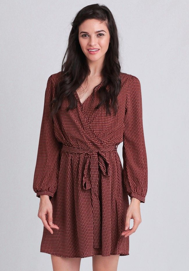 Beautifully crafted in a luxuriously silky fabric, this rust-colored dress features a black, yellow, and beige geometric print and a flattering surplice neckline. Finished with an elastic waist...