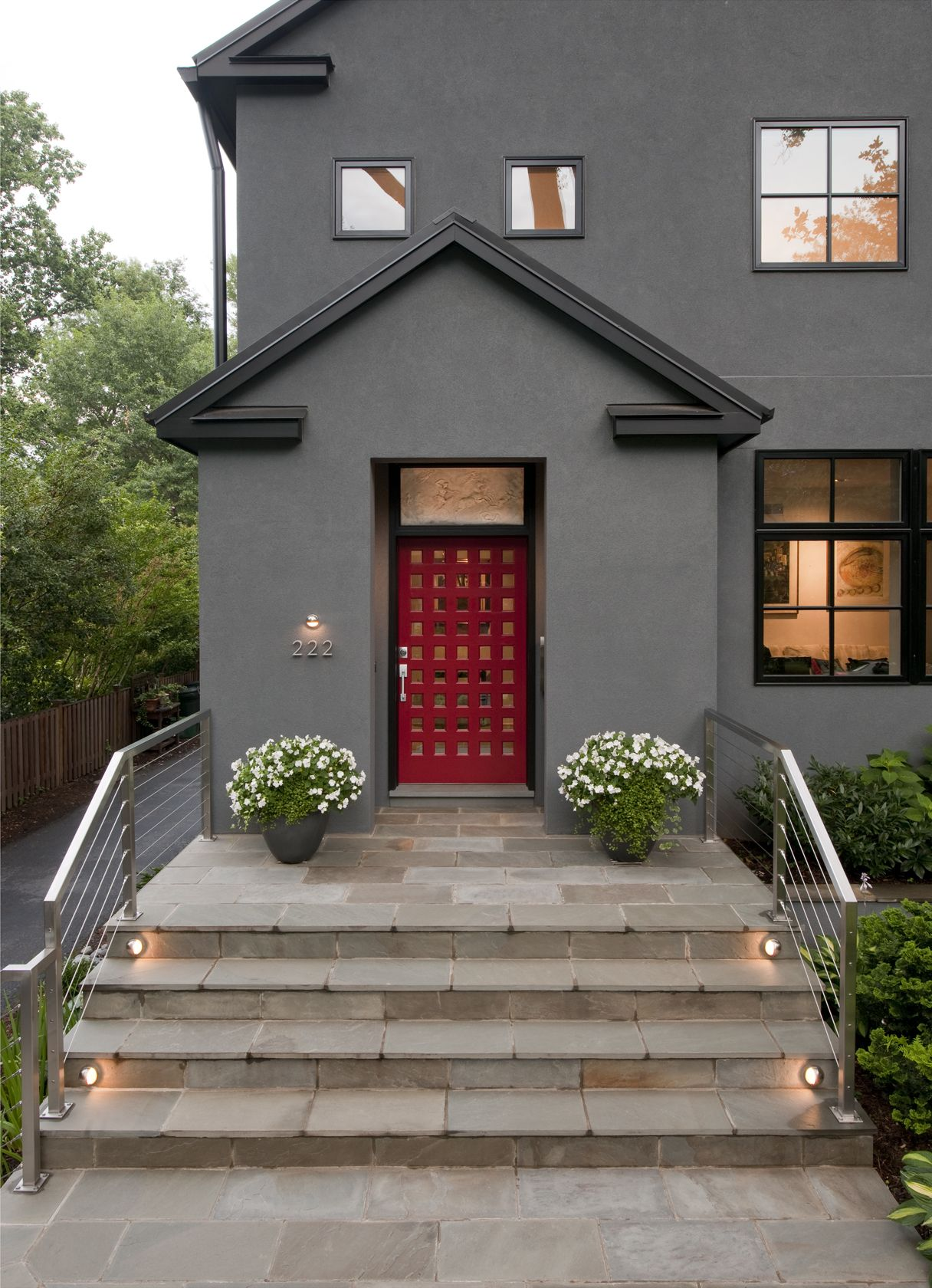 Stone Steps Lead To A Contemporary Red Door With Unique Window