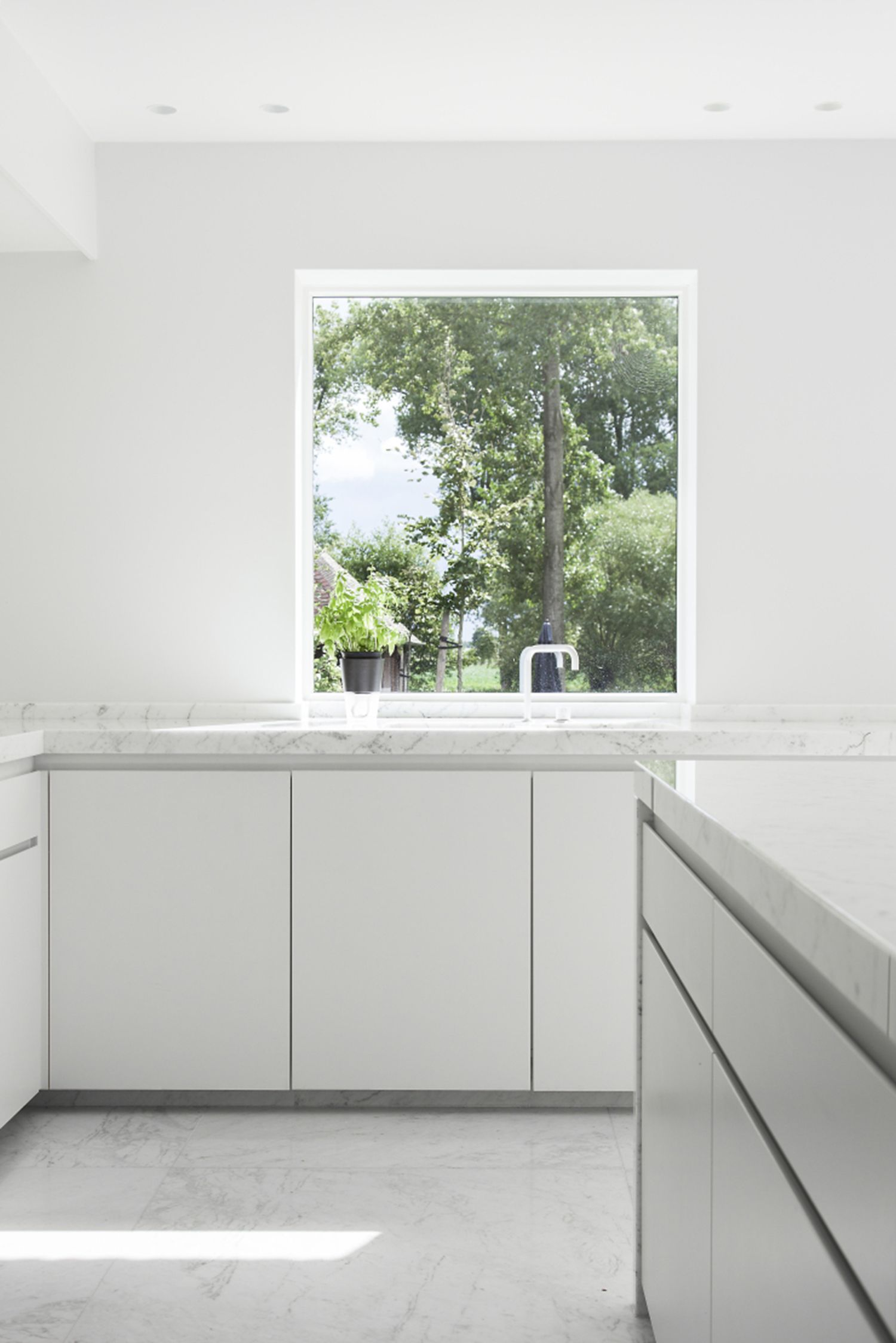 view! a great view to have when you're doing the dishes. This bright kitchen wouldn't look the same with lots of colours. Keeping this kitchen very light makes you focus on the outside. What a beautiful garden view.