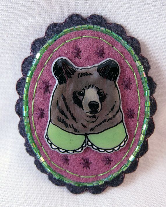This lovely piece of wearable art is constructed of wool-blend felt, embellished with hand stitching and beading. It features an original hand drawn and painted illustration of a smart brown bear wearing a scalloped collar. Crafted with care and great attention to detail, it can be worn as a brooch or as a pendant. Just put a piece of ribbon or your favorite chain through the felt loop on the back to wear as a pendant.  Approximately 2 3/4 x 2.  The illustration is created by hand with…