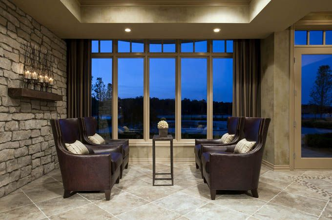 This stunning lower level's first concept was the custom stone wall. The custom  leather chairs overlook the lake. Tutto Interiors Cheryl Nestro - Northville, MI