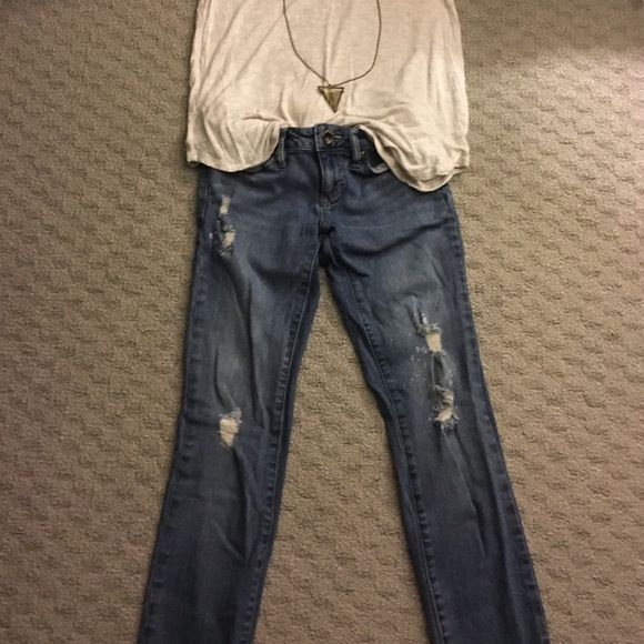 Light wash skinny jeans with rips These light skinny jeans fit at the waist. They have some intentional tips on the front and the back. There are also some intentional bleach spots. They go past the ankle in length (I am 5'3). Sorry for the wrinkles! I will get them out! Size 1 Bullhead Jeans Skinny