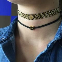 """The Love Choker by Gina Cueto features a gold overlay sliding charm with the word """"LOVE"""" engraved in the center. This contemporary twist on the classic charm necklace features a double faux leather co"""