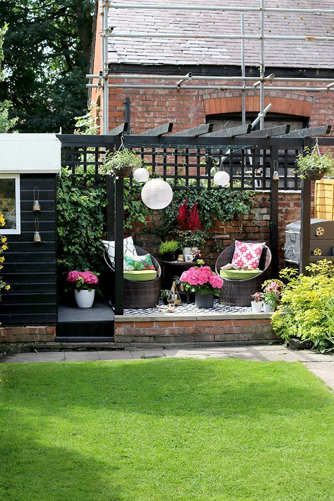 Black shed and pergola patio area with hanging lanterns in pink and green am nagement de - Baraque de jardin ...