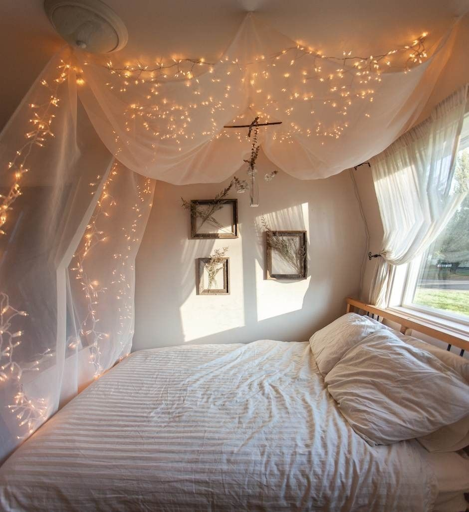 Bed with window behind it  a string or two of lights behind netting hello apartment