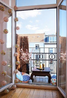 Effektiv afskærmning mod vind og nabo-kig med stråmåtter. To sækkestole og et lille sofabord giver plads til hygge på den lille altan