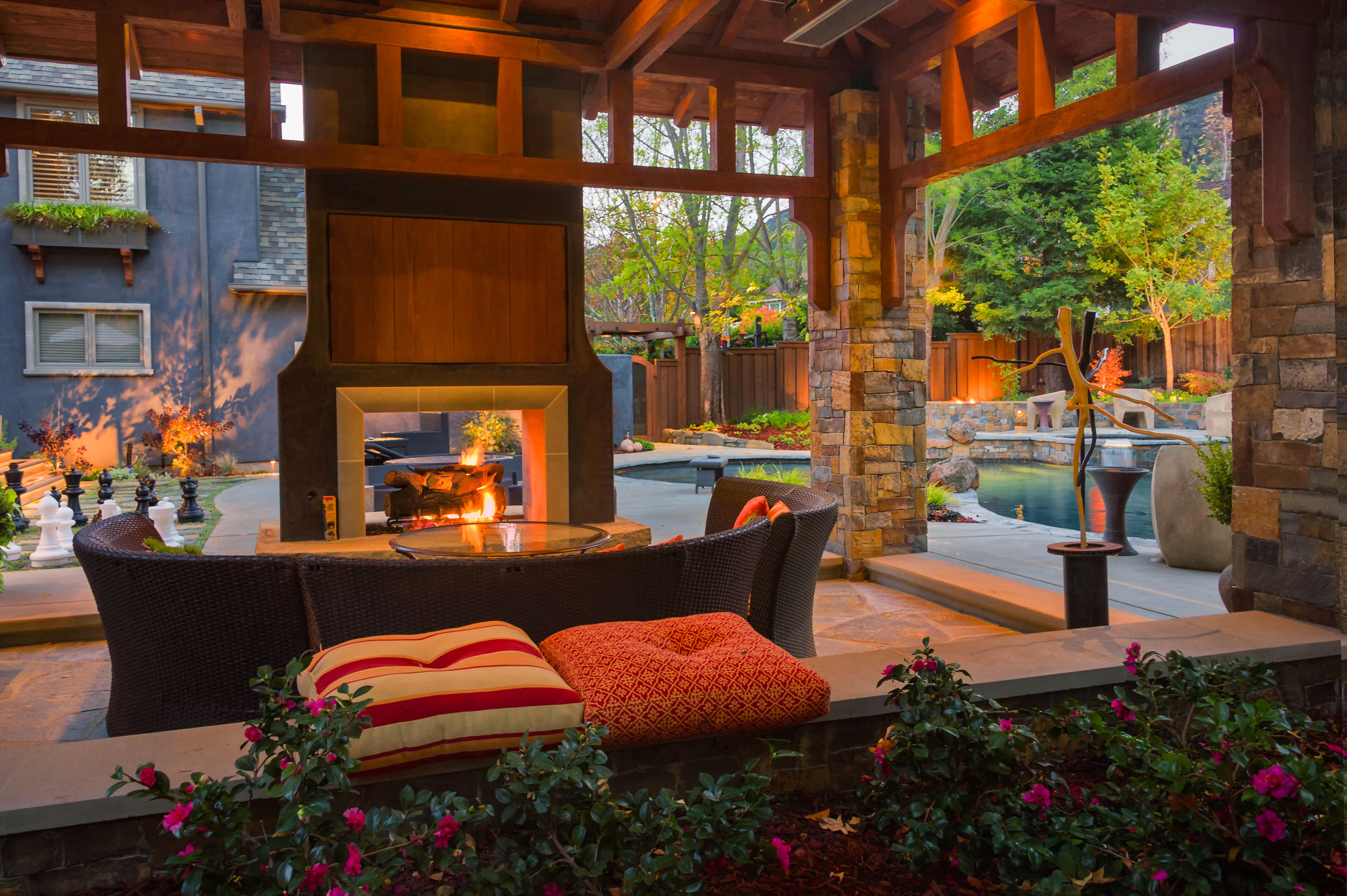 backyard patio with wood and stone pavilion two sided fireplace