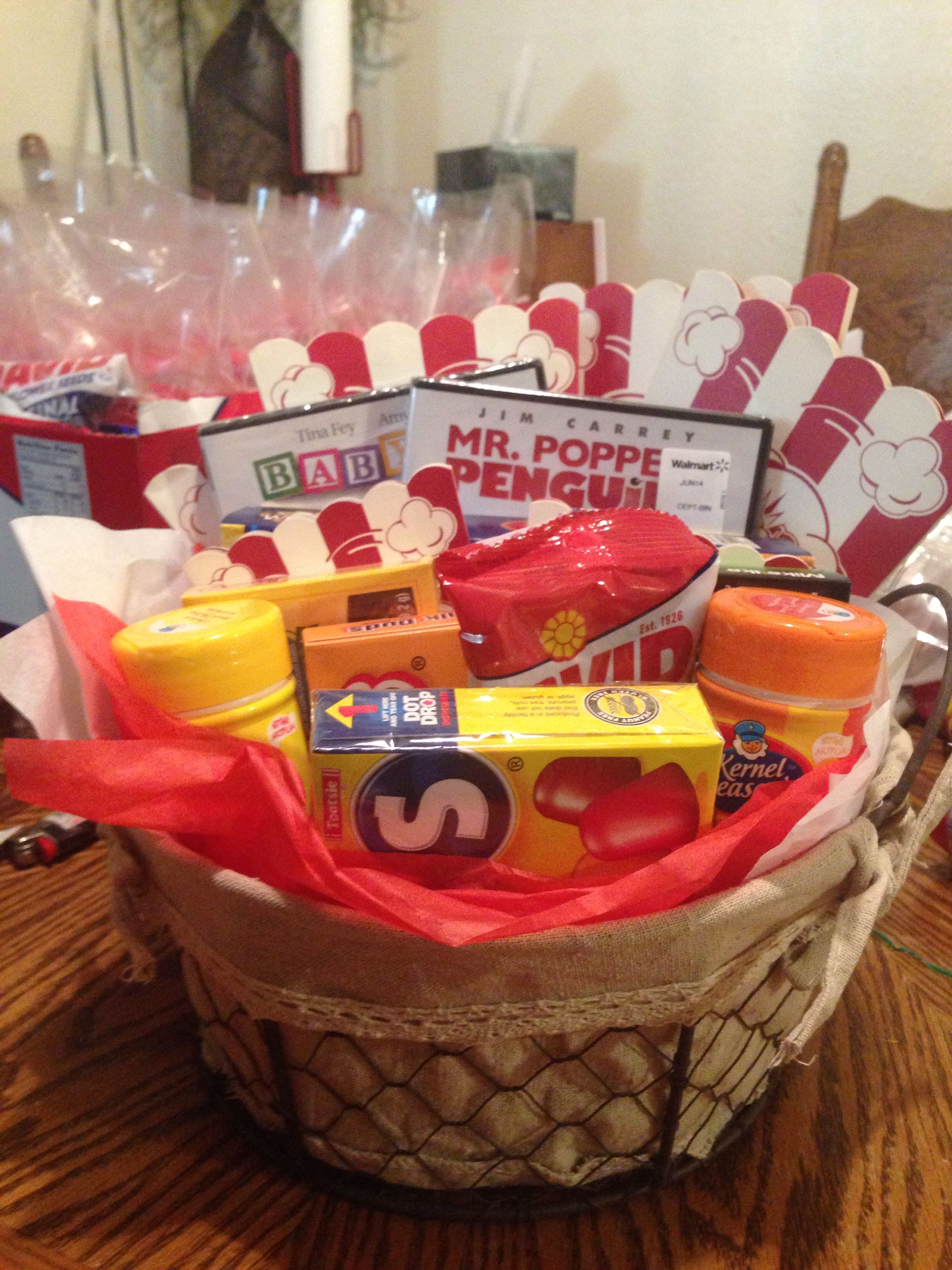 here is the diaper raffle prize for my baby shower a movie night in a basket complete with popcorn popcorn flavoring candy sunflower seeds