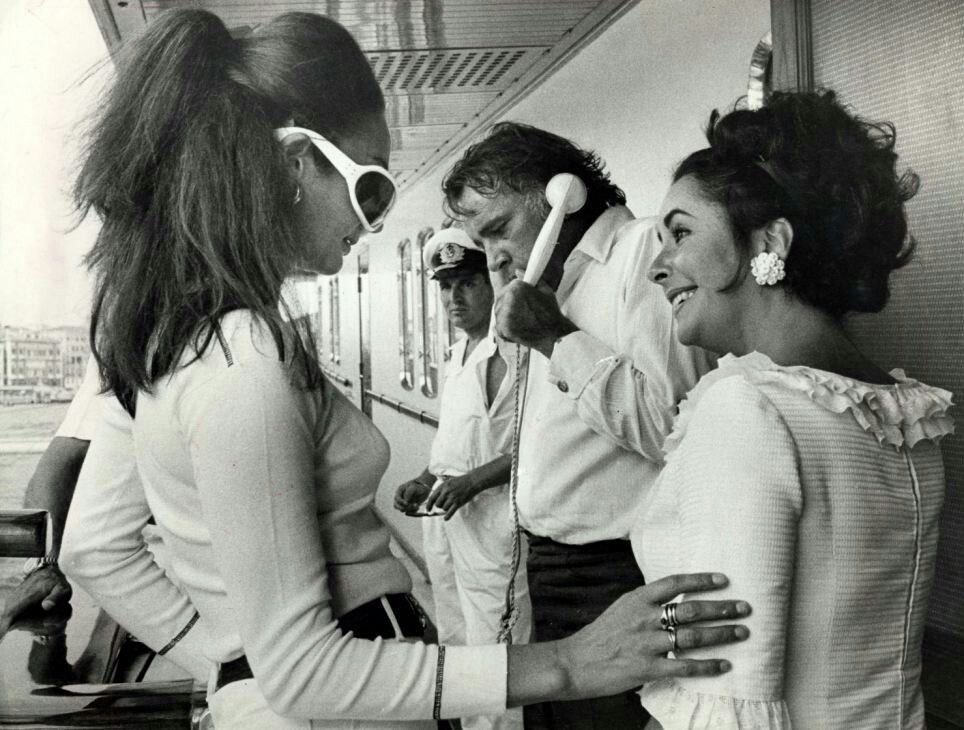Richard Making A Call To London While Elizabeth Chats With The Vicomtesse De Ribes On Ari Onassis Yacht At A Part Aristotle Onassis Elizabeth Taylor Christina