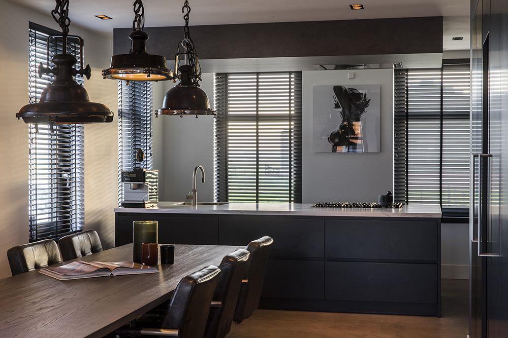In de zwartbruine keuken met marmeren keukenblad zorgen de houten