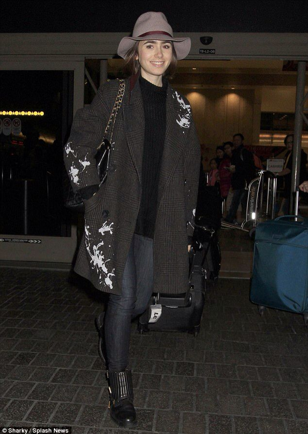 Lily Collins suffers a rare fashion misstep in paint splattered coat as she arrives at LA airport with mother in tow