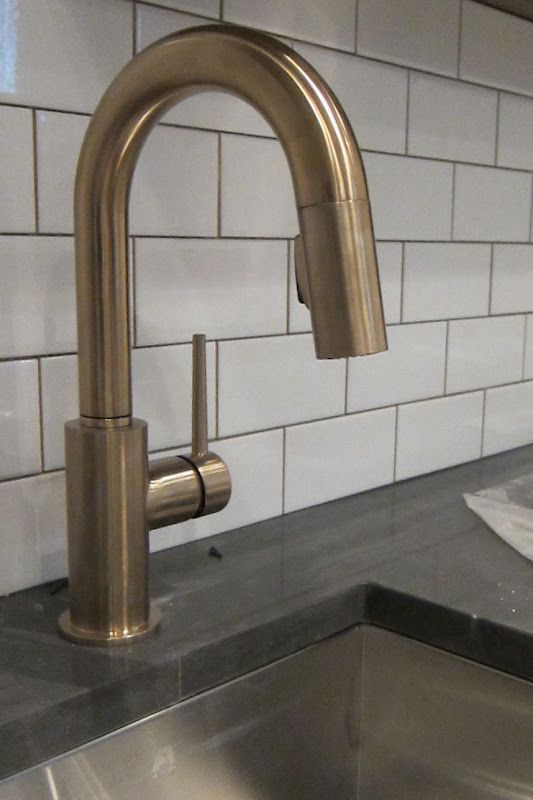 subway tile with grey grout, dark gray counter, brass faucet