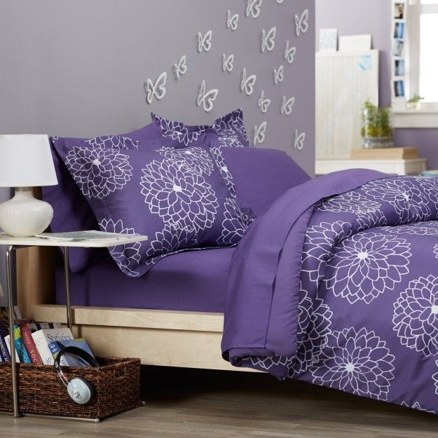 a purple comforter set covered with big