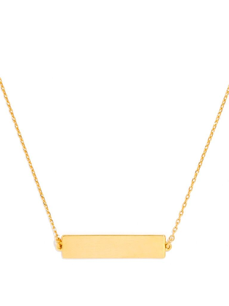 A slim metallic bar pendant lends clean, architectural lines to a layered necklace look.