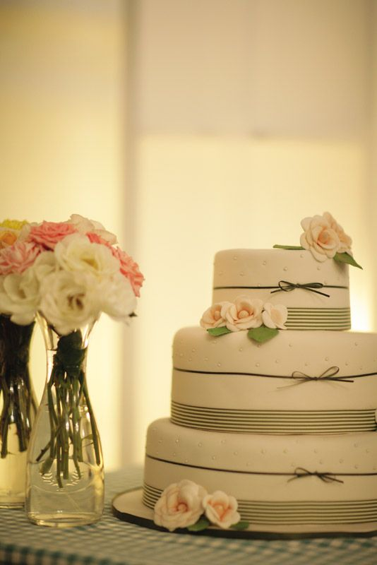 Wedding cake decorated with striped ribbon to match the table runners and soft pastel icing flowers.