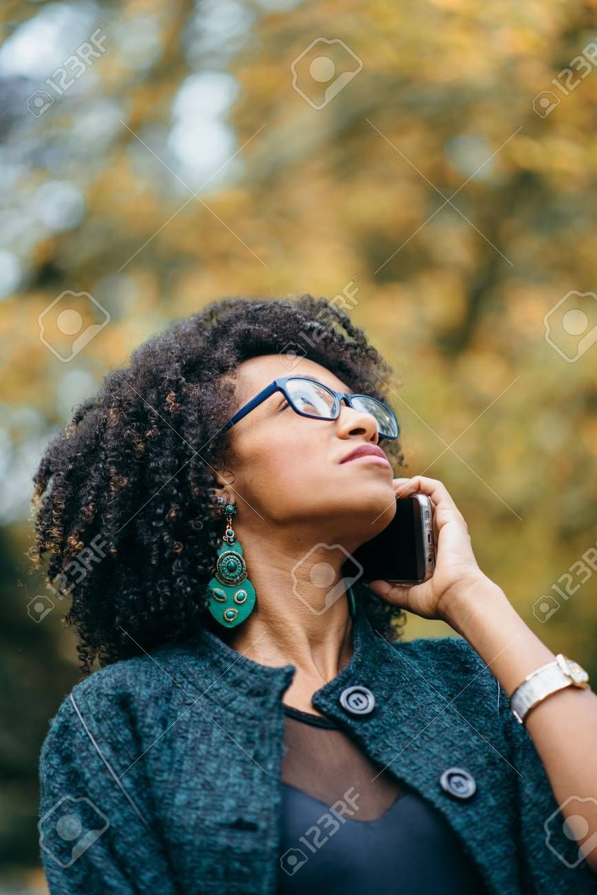 Young Black Woman Talking On Cell Phone Outside At The Park In