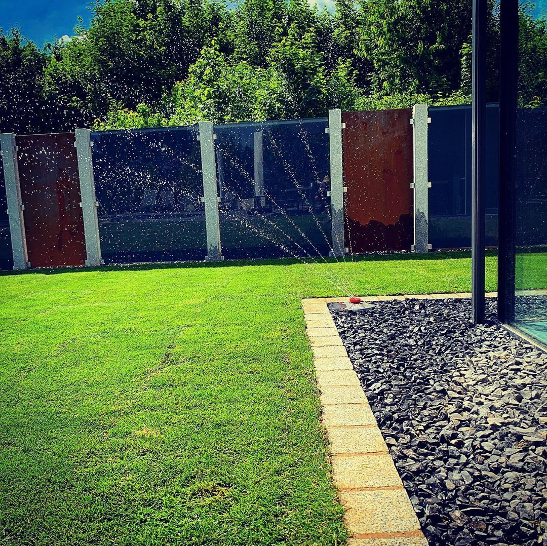 Sichtschutz aus Cortenstahl und Glas mit Granitsäulen