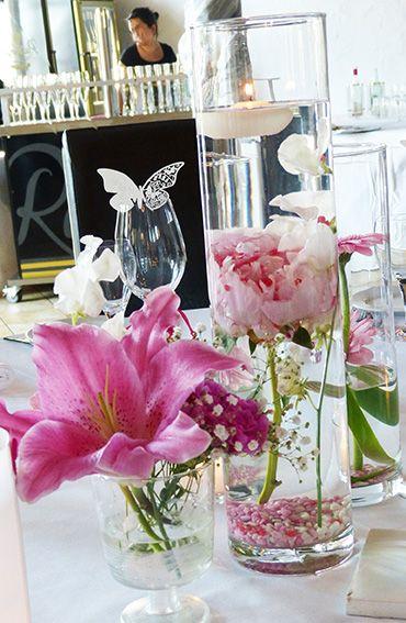 Zylindervase mit untergetauchten Blumen und Schwimmkerze