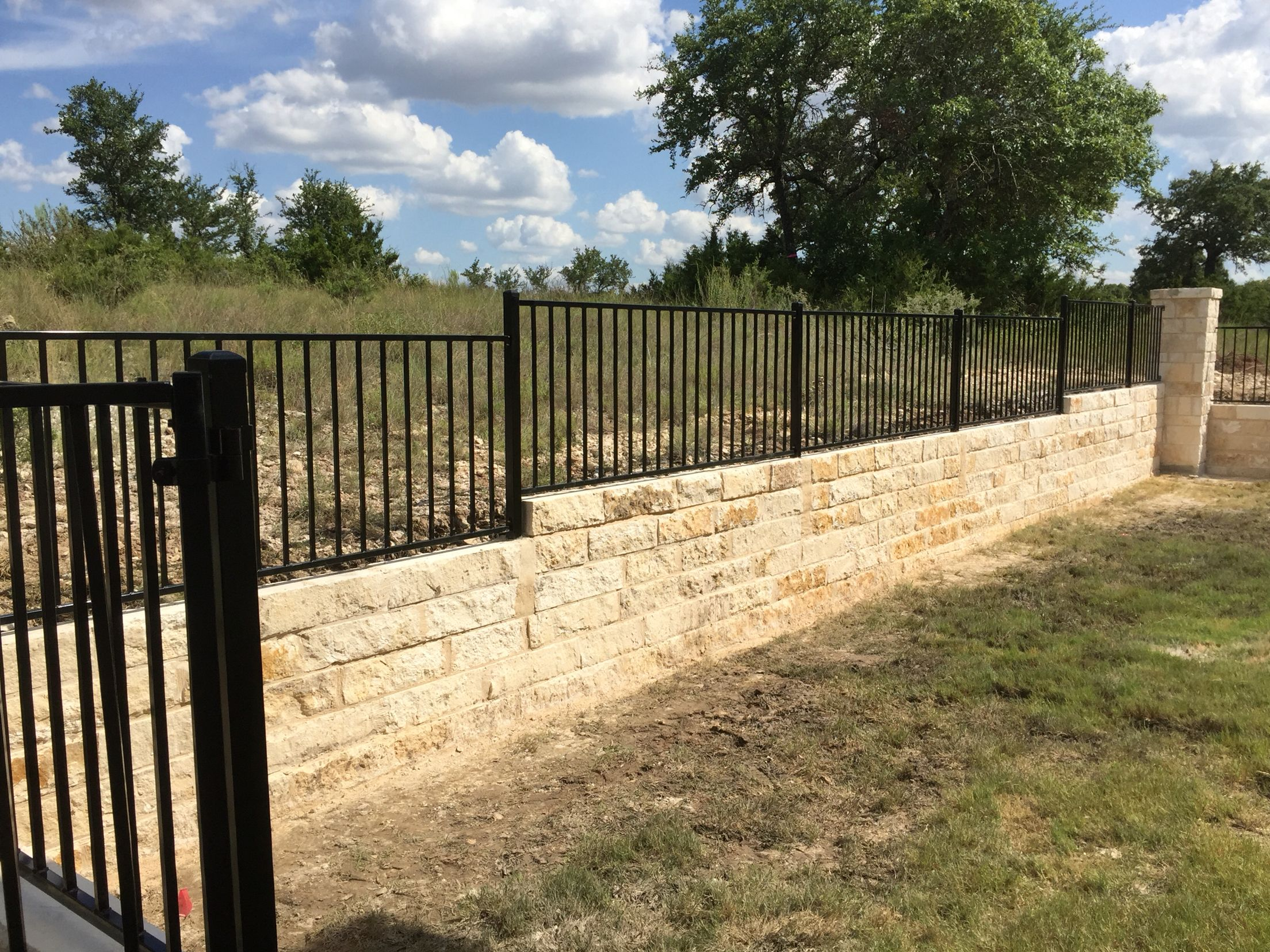 Wrought iron on limestone retaining wall | Pflugerville Pfence Co ...