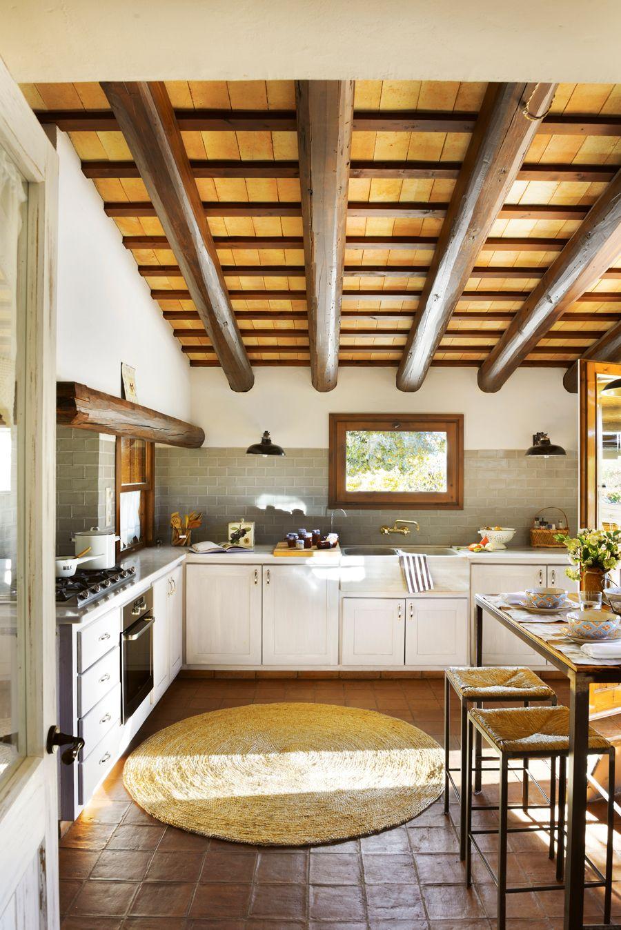 Cocina rústica con vigas, antepecho de azulejos, alfombra de fibra y ...