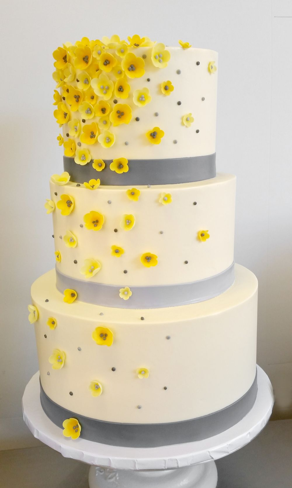 Gray ribboned wedding cake with yellow cascading blossoms (3-tier ...