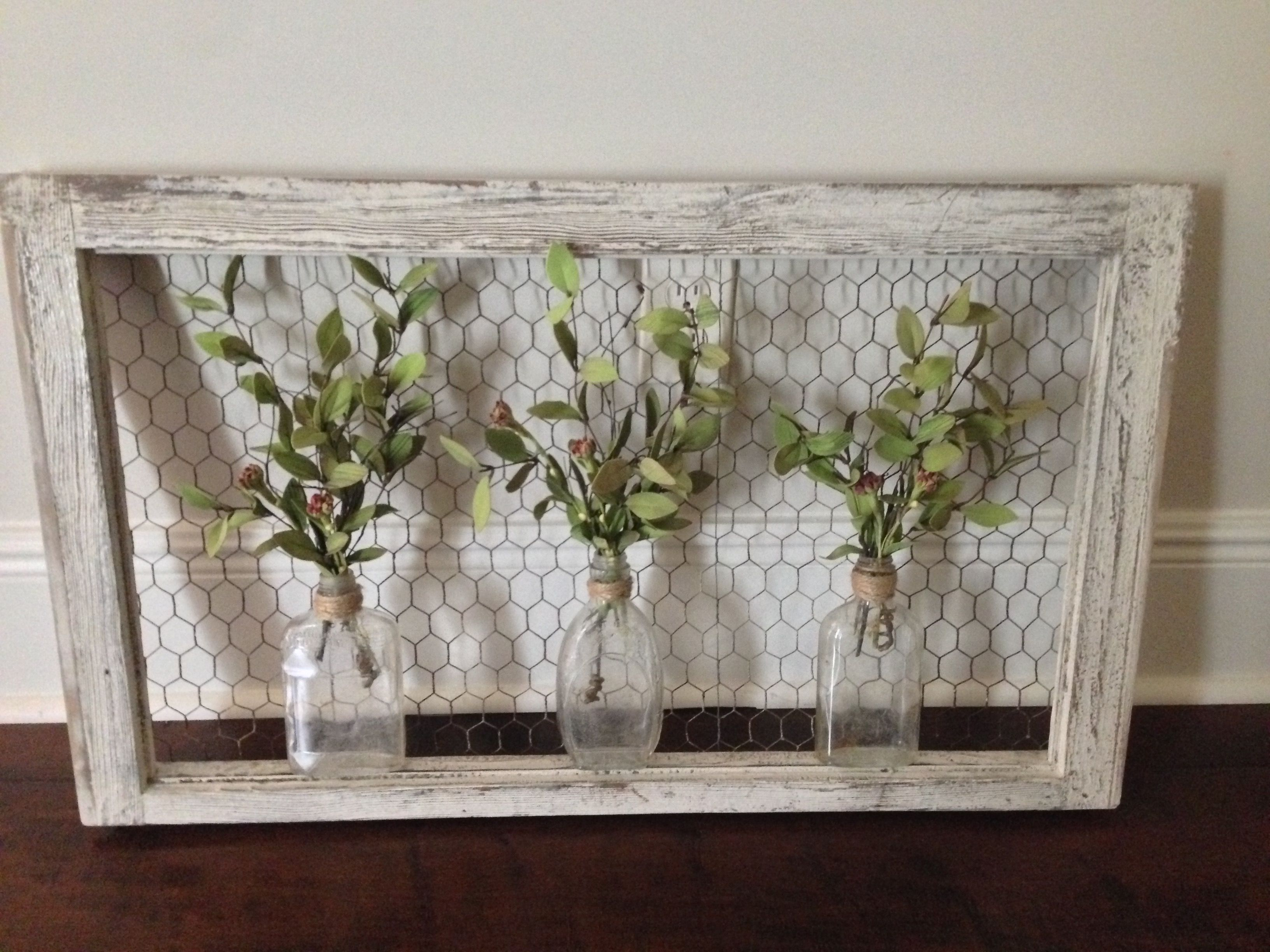 Wall art old window frame chicken wire old bottles and greenery