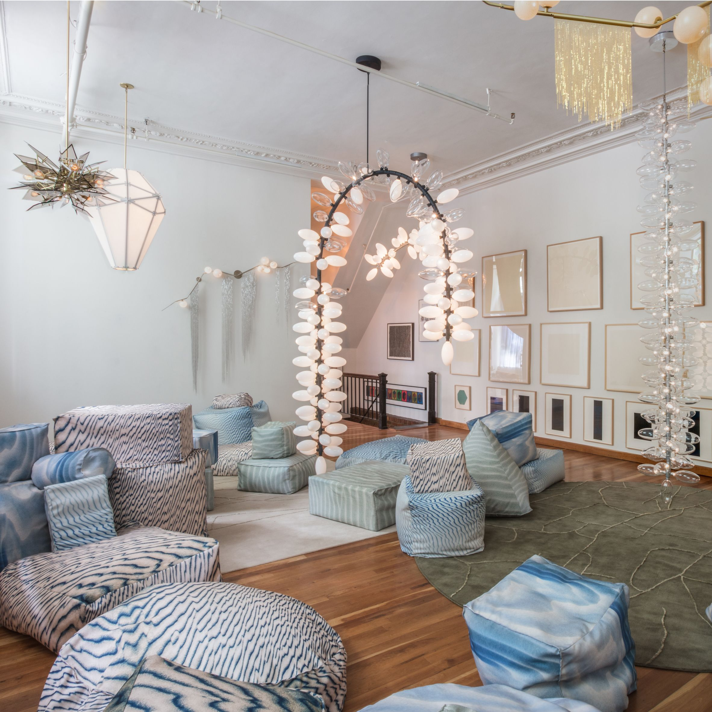 Wall lamps with draping metal chains by New York designer Lindsey Adelman and huge modular lights that bend in different directions by her colleague Karl Zahn feature in a tropical-themed display.