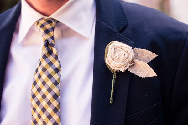 Groom wearing yellow and dark blue plaid tie with a tan linen boutonniere shaped as a rose