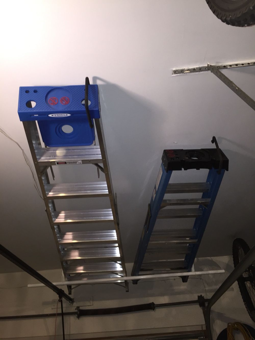 Easy Ladder Storage Above The Garage Door Using A Clothes