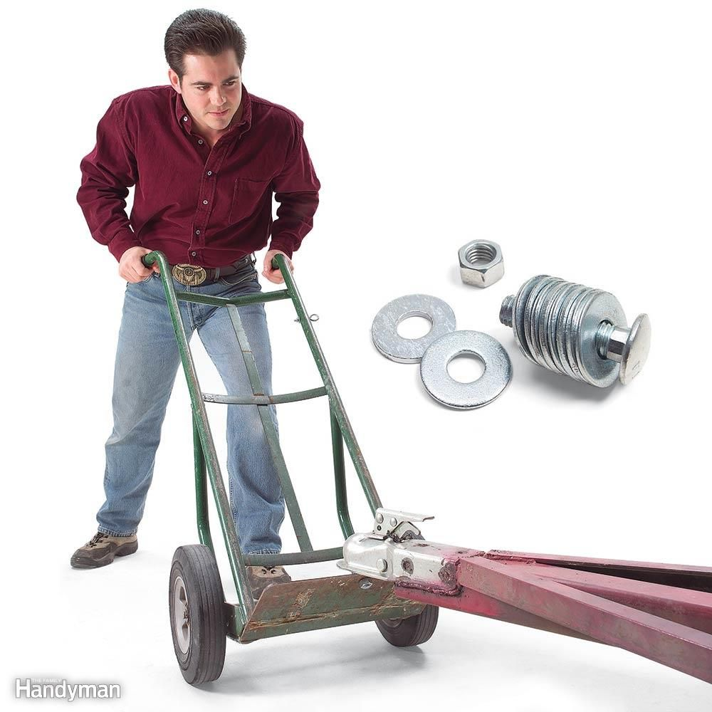 If you have a bad back, forget the lift-and-lug method. Instead, drill a hole in a dolly and add a 3-in. bolt and a stack of washers to create a knob. Slip that knob under the hitch socket, lift, and push or pull.