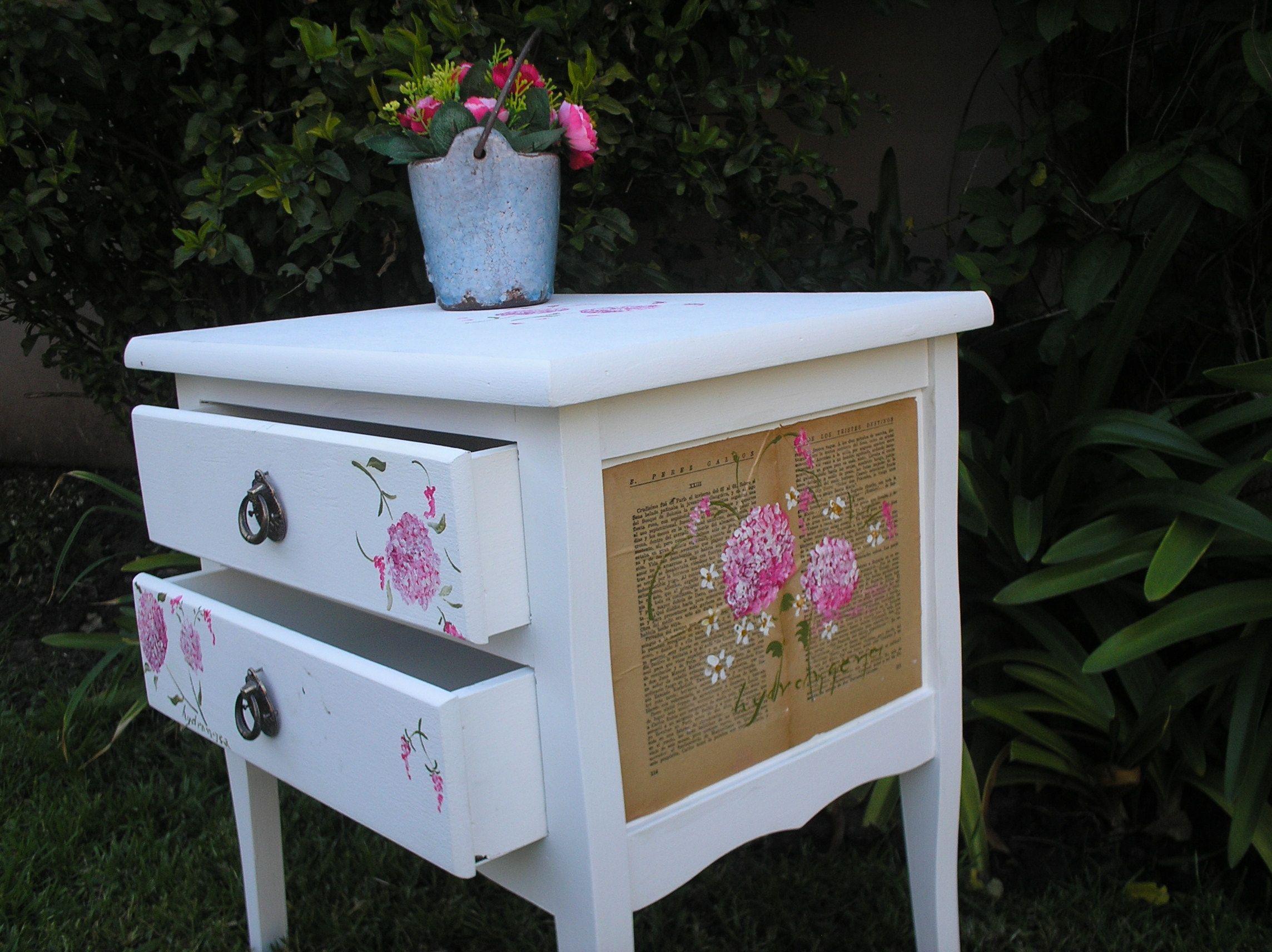 Antigua mesa de luz reciclada con detalles de flores pintadas a mano sobre hojas de antiguos libros