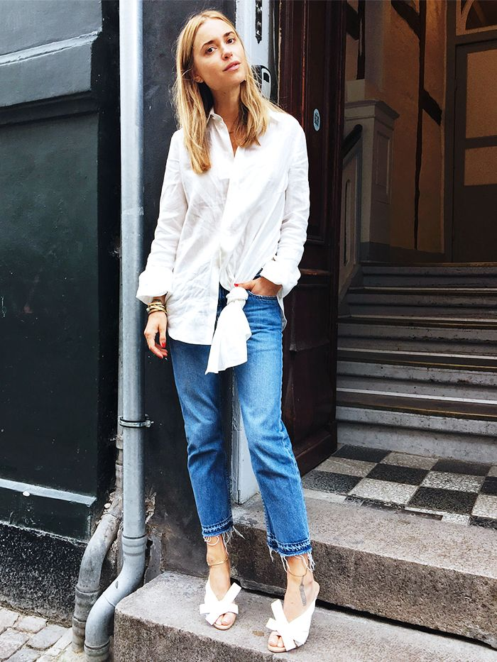 91e130766 Blogger Pernille Teisbaek wears a knotted white button-down blouse,  distressed cropped jeans, white mules, and stacked gold jewelry