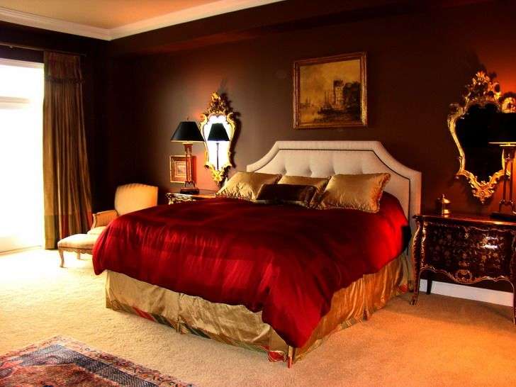 Red bedroom paint with green accents. Dark wood furniture.
