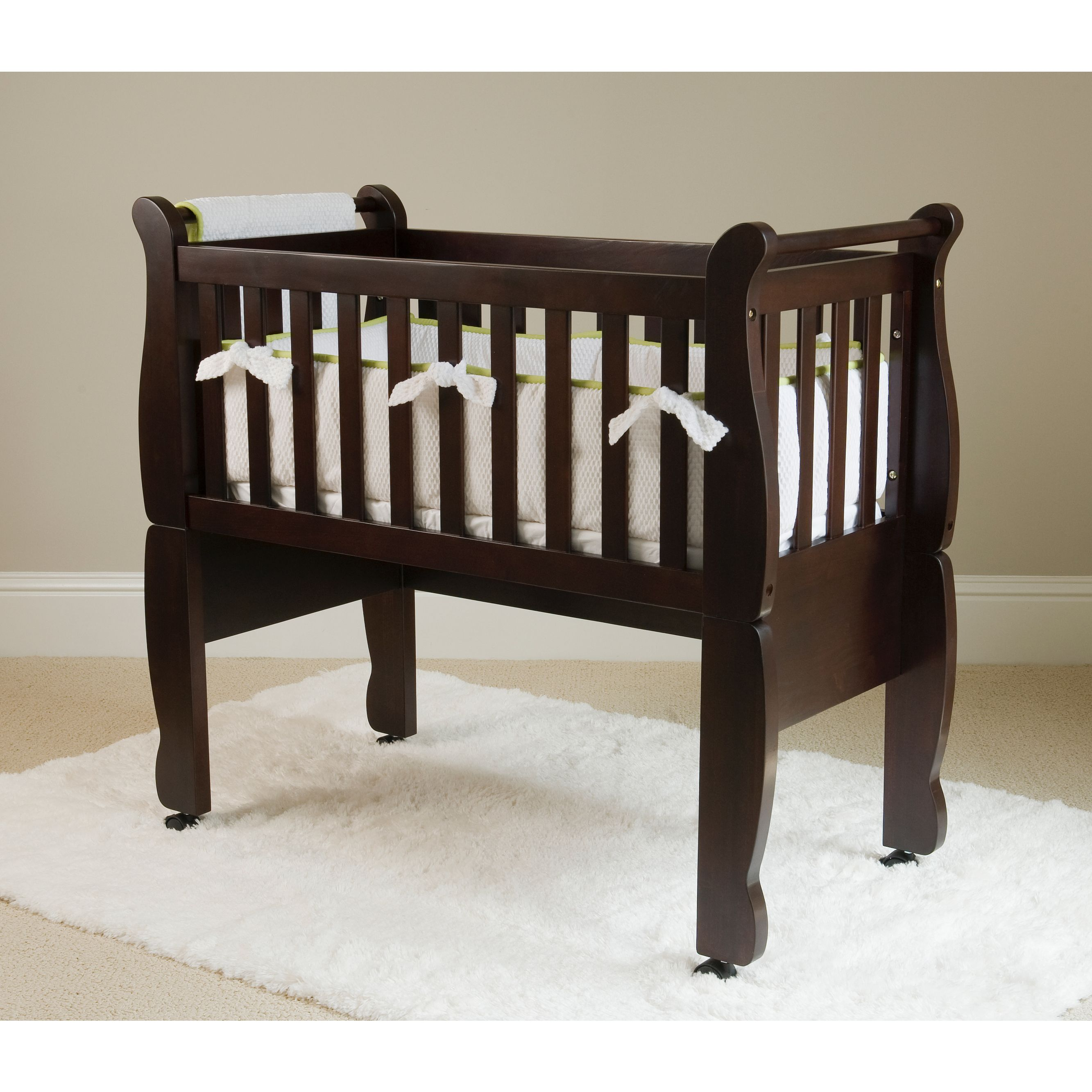 This versatile and elegant baby crib includes a wheel or rocker feature for the legs and a soft fitted mattress. Finished with New Zealand pine and an espresso stain, this cradle will fit in any home perfectly.