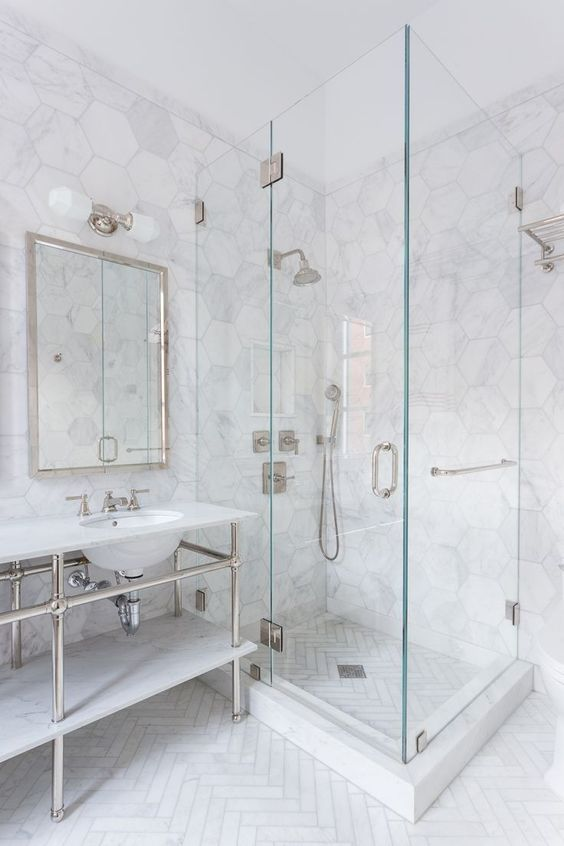 a chic bathroom with white marble hex tiles and a herringbone pattern on the flo a chic ba a chic bathroom with white marble hex tiles and a herringbone pattern on the fl...