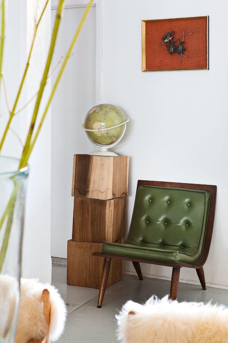 Discreto - AD España, © Manolo Yllera Una pequeña obra sobre una silla de cuero verde del Chelsea Flea Market, como el globo vintage sobre trozos de madera en From The Sources, en la casa de una pareja de estilistas en Nueva York.