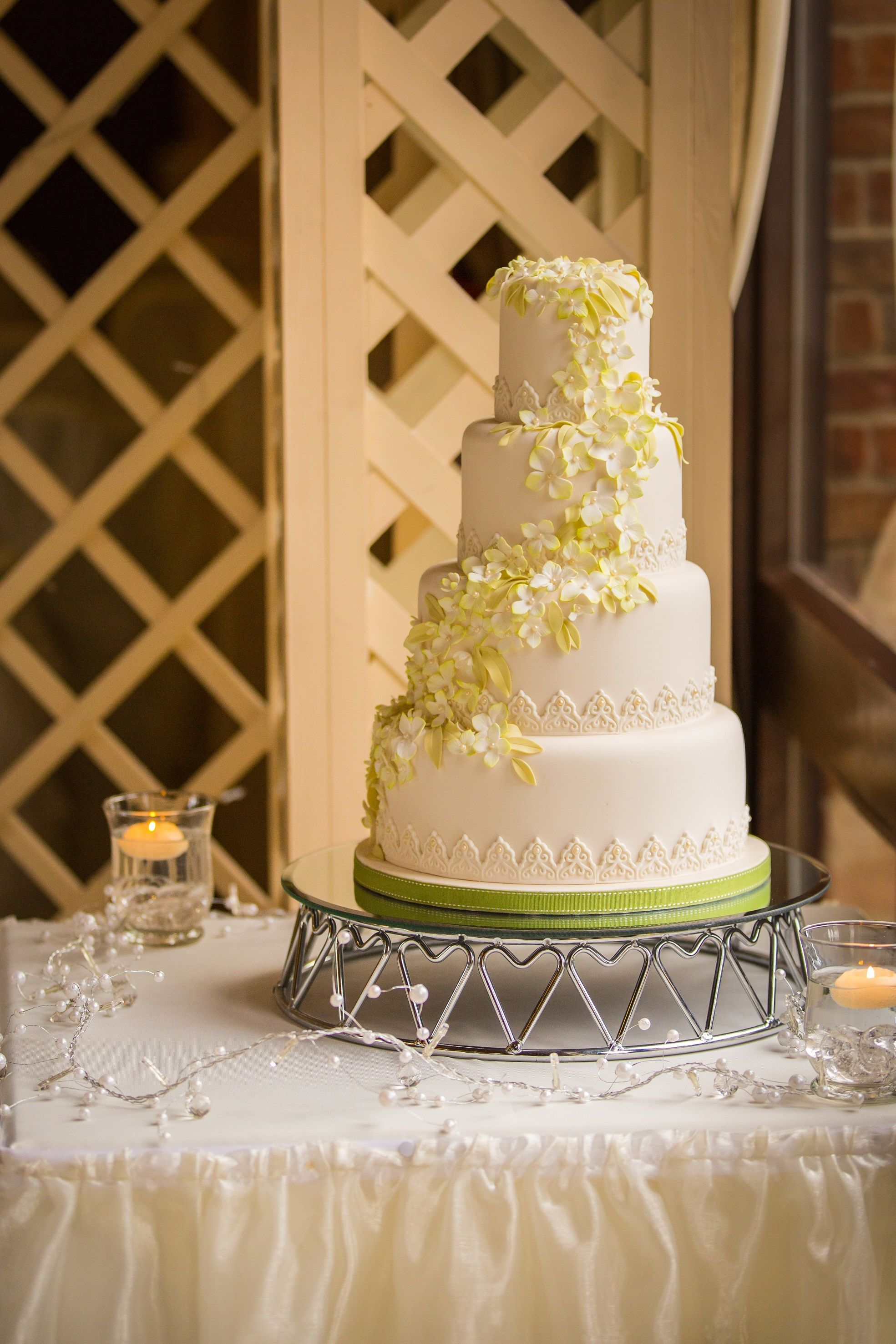 Beautiful ivory cake with green accents, surrounded by pearl fairy ...