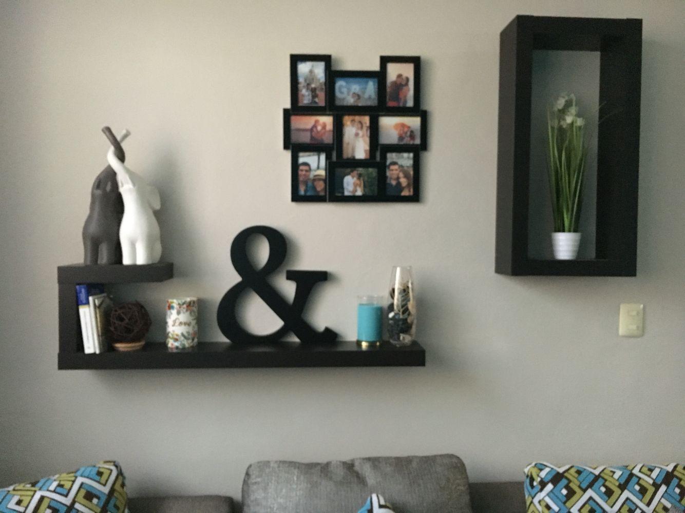Decoración en sala, con repisas, letras, velas y fotografías