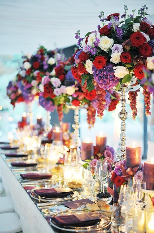 Opulent Centerpieces Of Red White And Purple Roses Hydrangeas Dangling Grapes Make