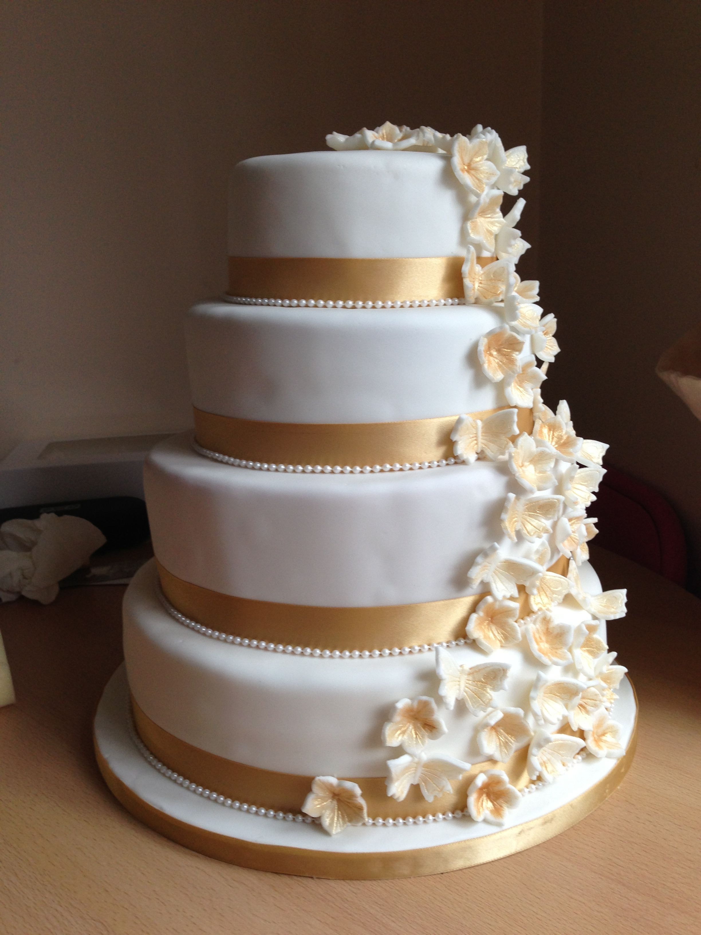White And Gold Wedding Cake With Cascading Flowers And