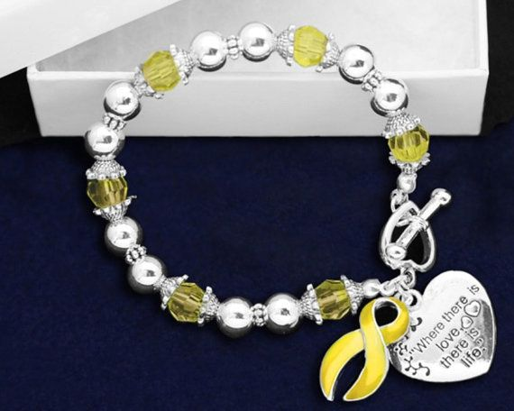 This yellow ribbon bracelet has silver and yellow beads along with 2 charms. A heart charm that is engraved with the words Where There is Love