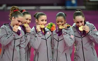 You've just won a gold medal! So why are you trying to eat it? (Emmanuel Dunand / AFP - Getty Images)