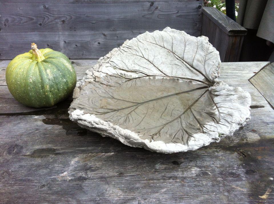 Vogel badje gemaakt van beton met de vorm van een rabarberblad of ander groot blad met dikke nerven.