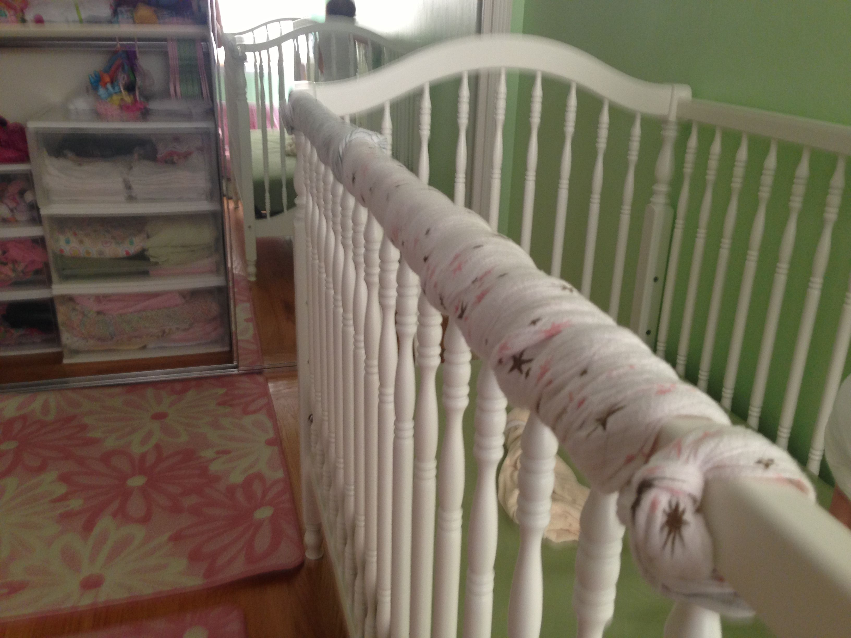 Use a swaddling blanket as a DIY crib rail teething guard