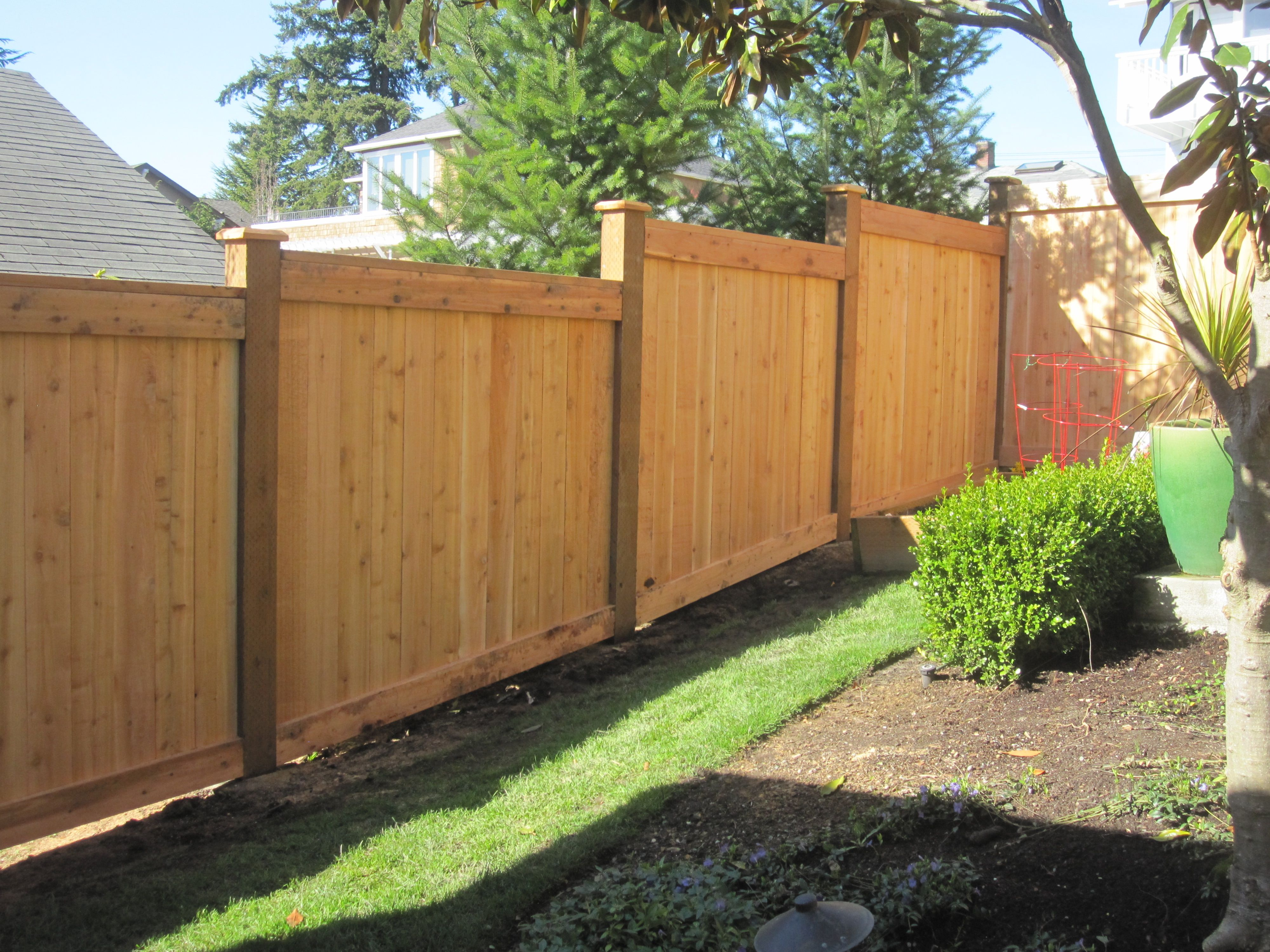 Stepped full panel cedar wooden fence with grade